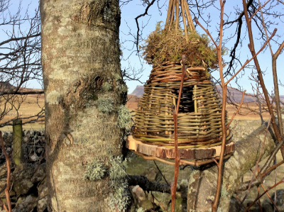 teepee bird house with moss willow and a wooden base